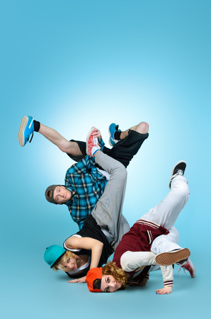 street party: Group of young modern dancers dancing together with fun. Studio shot.