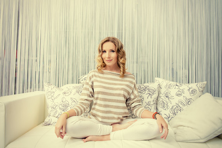 yoga pillows: Happy young woman having a rest in her bedroom and doing yoga exercises. Home interior, furniture. Lifestyle.