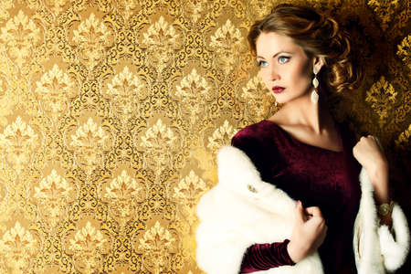 Elegant young woman in  evening dress and mink fur jacket posing in vintage interior. Jewellery.  Fashion shot. Stock Photo