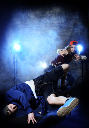 Two modern dancers over grunge background. Hip-hop. Urban, disco style. photo