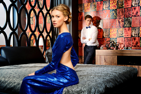Beautiful woman and young man in elegant evening dresses in a classic interior, bedroom. Fashion, glamour.