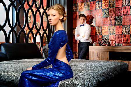 modelos hombres: Mujer hermosa y hombre joven en vestidos de noche elegantes en un clásico interior, dormitorio. Moda, glamour. Foto de archivo