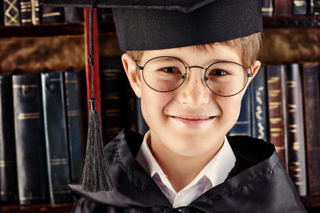 Smart boy stands in the library by the bookshelves with many old books. Educational concept. Science. Vintage style. photo