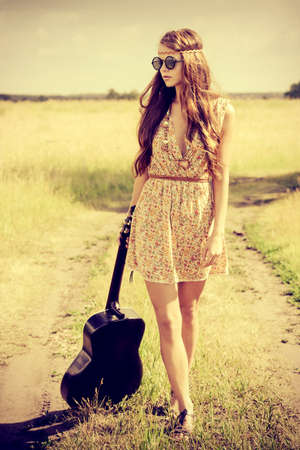 hippie: Romantic girl travelling with her guitar. Summer. Hippie style. Stock Photo