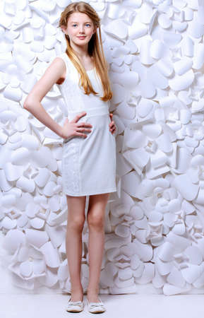 Beautiful blonde teen girl wearing white dress posing by a background of white paper flowers. Beauty, fashion. Full length portrait. photo