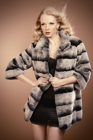 fur coat: Fashion shot of a beautiful blonde woman wearing jewelry and fur coat. Studio shot. Stock Photo