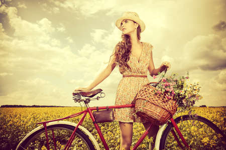 Romantic young woman stands in a field with her bicycle and a basket with wild flowers. Summer.