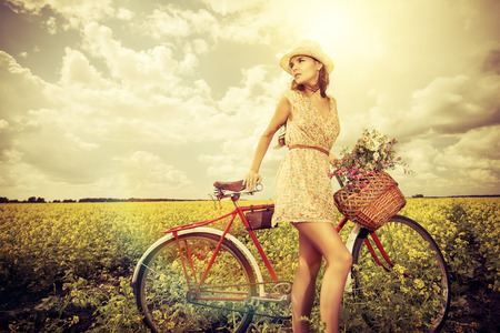 Romantic young woman stands in a field with her bicycle and a basket with wild flowers. Summer. photo