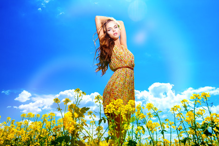 Happy young woman standing in a field of blooming yellow flowers. Summer. photo