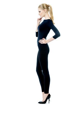 In voller Länge Porträt einer schönen schlanken weiblichen Modell in schwarz sitzende Kleidung posiert auf weißem Hintergrund. Schönheit, Mode. Körperpflege. Isolierte über weiß. Standard-Bild