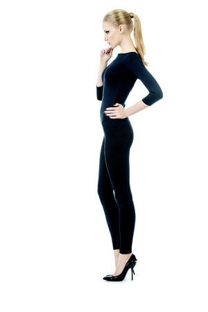 cuerpo femenino perfecto: Retrato de cuerpo entero de una hermosa modelo de mujer delgada con ajuste negro posando ropa sobre fondo blanco. Belleza, la moda. El cuidado del cuerpo. Aislado en blanco.
