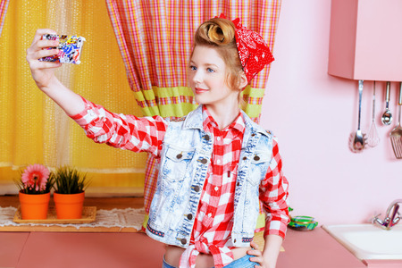 Pretty pin-up girl teenager taking picture of herself on a pink kitchen. Beauty, youth fashion. Pin-up style. Selfie. photo