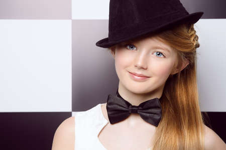 Elegant teen girl wearing white dress, black hat and a bow-tie posing on a background of black and white squares. Youth fashion. photo