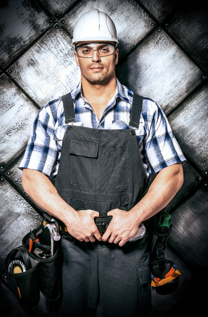 costruction: Handsome costruction worker wearing uniform and tools over grunge industrial background. Job, occupation. Stock Photo