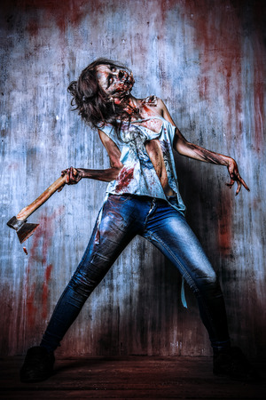 hand in hand: Scary bloody zombie girl with an ax. Halloween.
