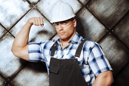 job occupation: Handsome muscular costruction worker wearing uniform over grunge industrial background. Job, occupation. Stock Photo