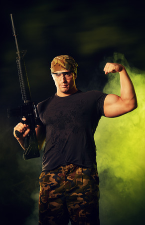 courageous: Courageous soldier in camouflage holding automatic rifle. Military.
