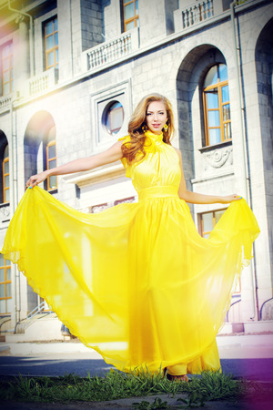 Romantic young woman in beautiful yellow dress walking on the street. photo