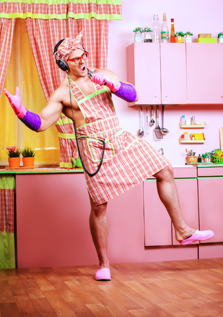 kitchen aprons: Funny and handsome muscular man in an apron and headphones singing into a microphone in the pink kitchen. Love concept. Valentines day. Womens day.