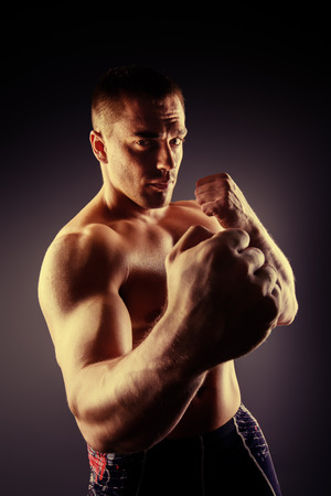 fighting arts: Strong muscular man fighting with fists. Martial arts. Fist fights, boxing. Bodybuilding. Black background.