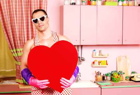 householder: Handsome muscular man in an apron holding big red heart. Pink kitchen. Love concept. Valentines day.