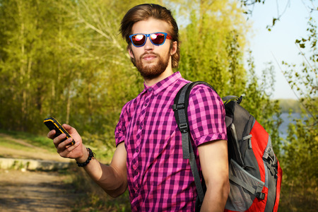active lifestyle: Handsome young man in casual clothes talking on the phone outdoor. Active lifestyle, tourism.