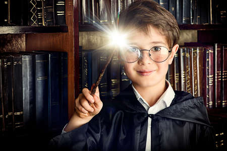 costume: A boy stands with magic wand in the library by the bookshelves with many old books. Fairy tales. Vintage style. Stock Photo
