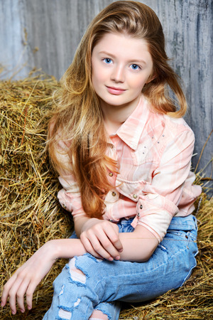 Pretty girl teenager in shirt and torn jeans posing on hay. Jeans fashion. Western style.