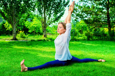 Beautiful young woman doing yoga, stretching exercise in the summer park. Healthy lifestyle. Yoga. photo
