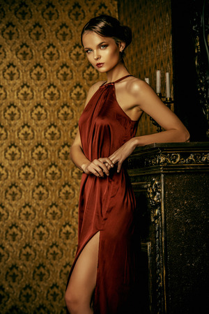 Romantic young woman in evening dress posing in vintage interior. Classic luxurious interior. Fashion shot. photo