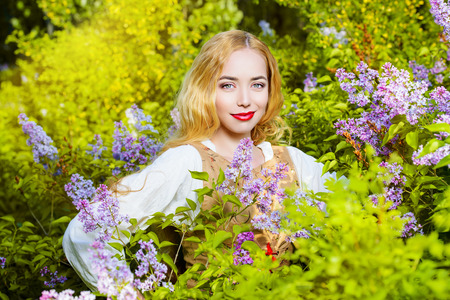 Lovely young woman with magnificent blonde hair near blooming lilac. Countryside. photo