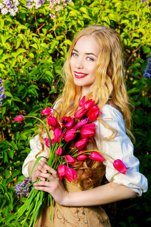 Happy young woman with magnificent blonde hair holding a bouquet of tulips. Countryside. photo
