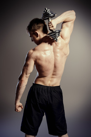 dorsi: Athlete man doing exercises with dumbbells. Bodybuilding. Muscles of the arms and back. Studio shot over black background.