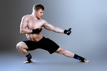 Muscular man in sportswear posing at studio. Bodybuilding. Martial arts. photo