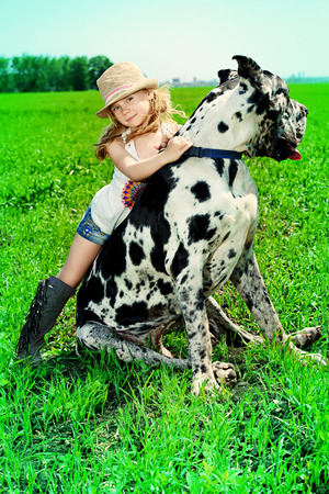 Happy little girl with her mastiff dog on a meadow in summer day. Countryside. photo