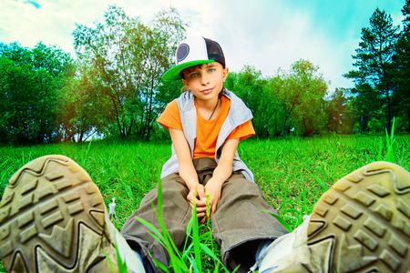 teen feet: Teenager boy sitting on a grass at a park. Summer day. Stock Photo