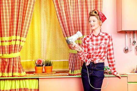 secador de pelo: Pretty estilos chica adolescente pin-up su pelo con un secador de pelo en una cocina de color rosa. Belleza, moda juvenil. Pin-up de estilo.