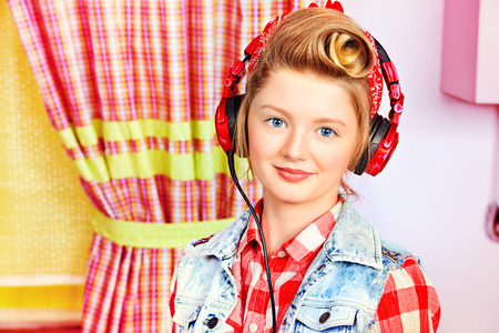 Lovely pin-up girl teenager listening to music in headphones on a pink kitchen. Beauty, youth fashion. Pin-up style. photo