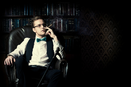 dandy: Elegant young man in a suit sitting in armchair and smoking a cigar. Vintage room. Fashion.