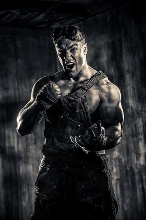 hombre sucio: Brutal hombre sucio musculoso expresar la agresi�n sobre el fondo oscuro del grunge. Industria minera. Mundo del futuro, el Apocalipsis. Sepia.