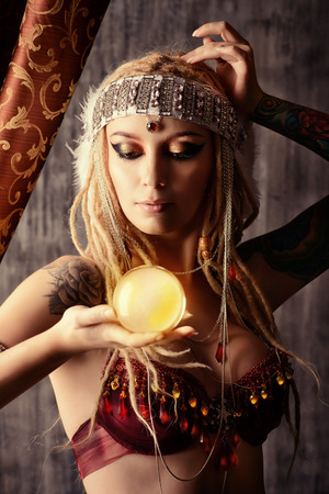 divination: Magnificent fortune teller holding crystal ball. Divination. Magic. Halloween.