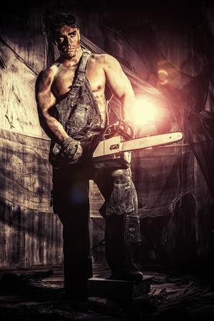 chainsaw: Handsome muscular man with a chainsaw over dark grunge background.