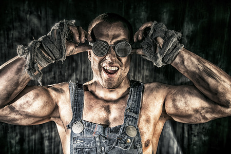 coal miner: Portrait of a strong muscular man coal miner standing over dark grunge background. Mining industry. Art concept.