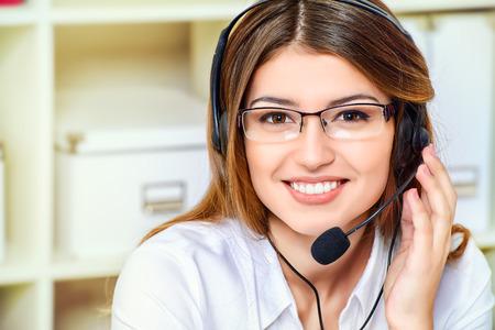 recepcionista: Joven operador de telefon�a Amistoso sonriente mujer surrort en su lugar de trabajo en la oficina. Auriculares. Servicio al cliente.