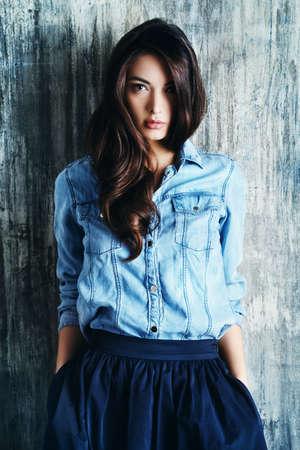 мода: Красивая чувственная женщина в джинсовой одежды стоит на гранж стену. Мода.
