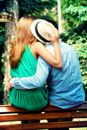 Young people tenderly kissing on a park bench. Love concept. photo