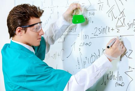 teorema: Un joven cient�fico la realizaci�n de investigaciones, haciendo experimentos y escribe los resultados. Foto de archivo