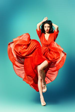 Fashion shot of the elegant woman in beautiful long dress posing in motion. Studio shot. photo
