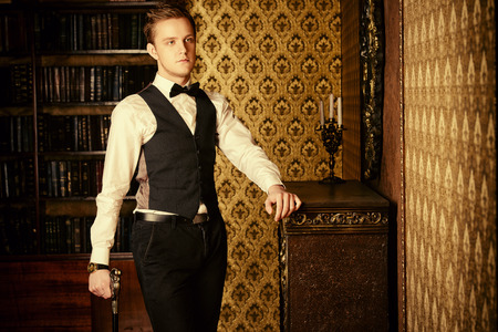 the vest: Young handsome man in evening suit stands by the fireplace in a room with classic vintage interior. Fashion.