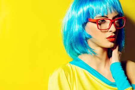 eye wear: Bright glamorous girl in vivid clothes and a wig alluring over yellow . Beauty, fashion. Cosmetics, hairstyle. Optics, eye wear.